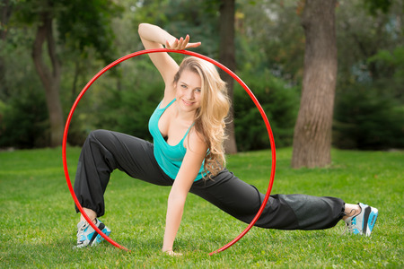Young female athlete inside  hoop in the park. Green grass backgruond photo