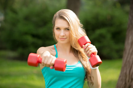 Young beautiful sports girl with dumbbells in the park on a background of green grass photo