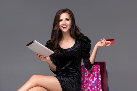 Schönes junges Mädchen, Zahlung per Kreditkarte für den Einkauf mit einem Laptop und Pakete vor grauem Hintergrund