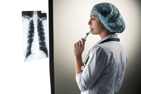 Image of attractive woman doctor looking at x-ray results on a gray background photo