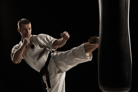 Man in white kimono training karate round kick in a punching bag over black background