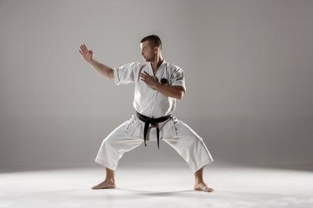 judo: El hombre en el kimono blanco y cintur�n negro de karate de formaci�n sobre fondo gris.
