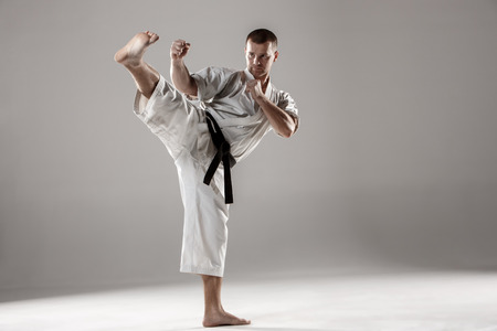karate fighter: Man in white kimono and black belt training karate over gray background.