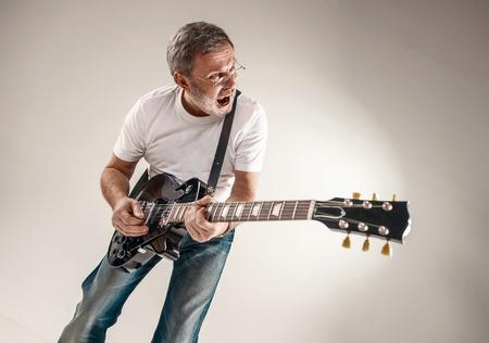 灰色の背景に音楽をエキサイティングなギター プレーヤーの肖像画