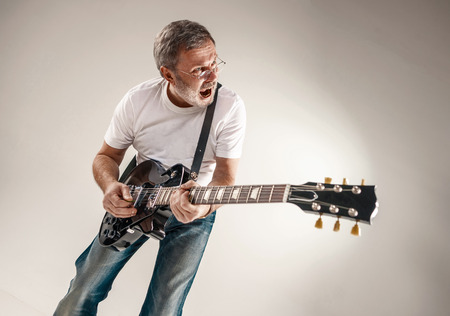 man playing guitar: Portrait of a guitar player exciting music on gray background