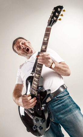 ecstasy: Portrait of a guitar player exciting music on gray background