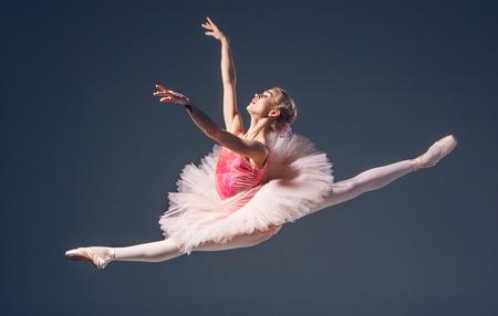 Hermosa bailarina de ballet femenino sobre un fondo gris. Foto de archivo