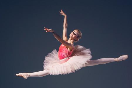 Krásná žena baletkou na šedém pozadí. Reklamní fotografie