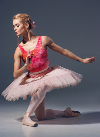 ballet: Retrato de la bailarina en actitud del ballet sobre un fondo gris.