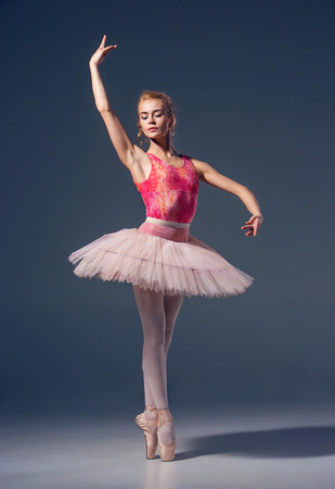 Portrait of the ballerina in ballet pose on a grey background. Ballerina is wearing  pink tutu and pointe shoes