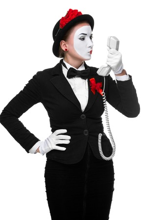 oncept: business woman as mime holding a handset isolated on white background. ?oncept of ?ommunication, the importance of negotiation in business