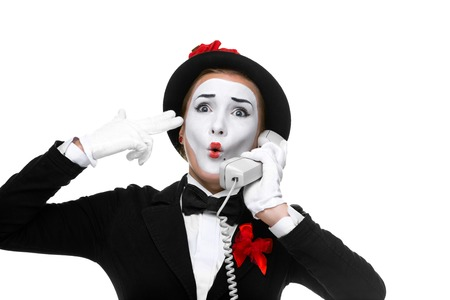 heard: Mime as business woman holding a handset isolated on white background. concept of despair heard