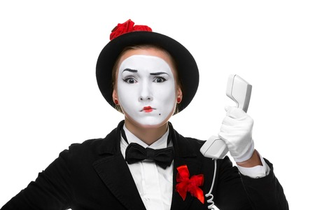perplexity: business woman as mime holding a handset, isolated on white background. Concept of perplexity Stock Photo