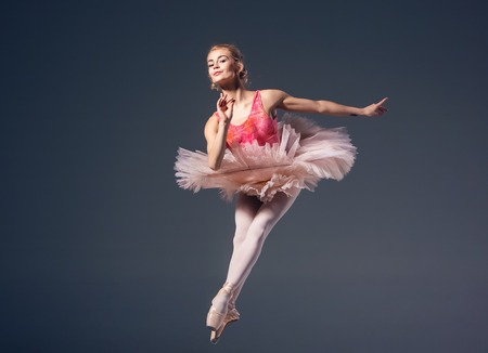 Beautiful female ballet dancer on a grey background. Ballerina is wearing  pink tutu and pointe shoes photo