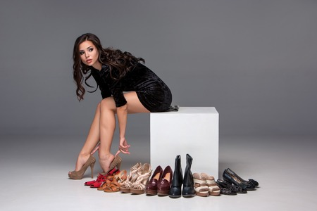 picture of sitting young attractive girl trying on high heeled shoes on a gray background