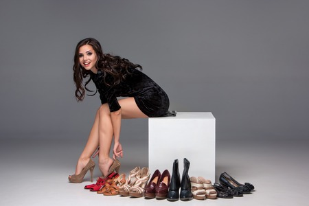 picture of sitting young attractive girl trying on high heeled shoes on a gray background photo