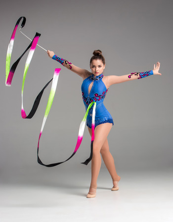 teenager doing gymnastics dance with colored ribbon on a gray background