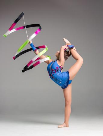 rhythmic gymnastics: adolescente haciendo gimnasia bailar con cinta de color sobre un fondo gris