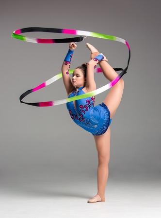 gymnastik: Teenager Turnen Tanz mit farbigen Band auf einem grauen Hintergrund
