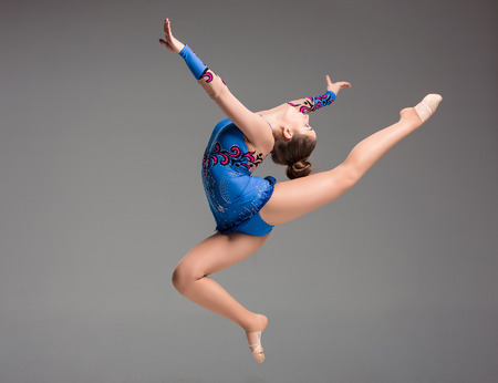 rhythmic gymnastics: teenager doing gymnastics dance  in  jumping on a gray background
