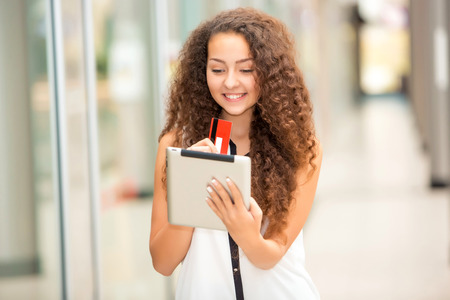 happy shopper: Beautiful young girl paying by credit card for shopping with a laptop against the background of the shopping center