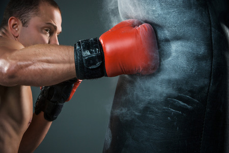sport training: Young boxer in red gloves boxing over black background Stock Photo