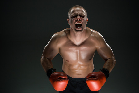 daring: Muscular man  in red gloves screaming and roar over black background Stock Photo