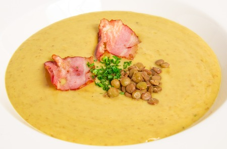 Pea soup with bacon on white background photo