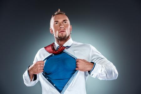 zakenman gedraagt zich als een superheld en scheuren zijn shirt uit op een grijze achtergrond Stockfoto