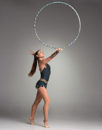teenager doing gymnastics exercises with gymnastic hoop on a gray background photo