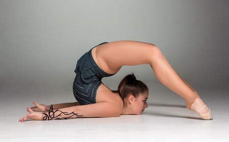 teenager doing gymnastics exercises  on a gray background photo