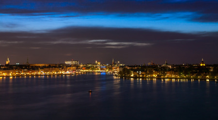 Stockholm cityscape at night with light reflection in water photo