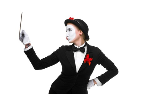 narcissism: business woman in the image mime holding tablet PC and  looking at a tablet PC as a mirror  isolated on white background. concept of concept of narcissism at work Stock Photo
