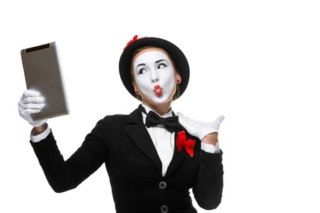 narcissism: business woman in the image mime holding tablet PC and  looking at a laptop as a mirror  isolated on white background. concept of concept of narcissism at work