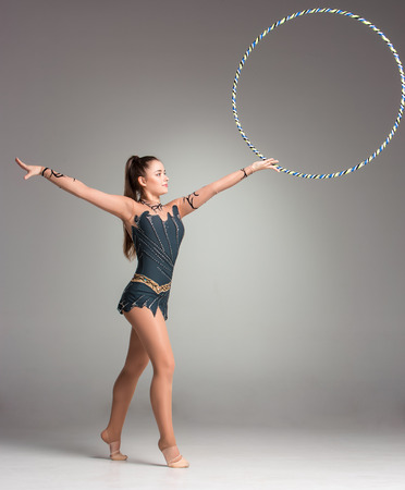 teenager doing gymnastics exercises with colorful hoop on a gray background photo