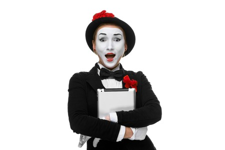 mimo: Mime sorprendido con tablet PC en sus manos aisladas sobre fondo blanco Foto de archivo