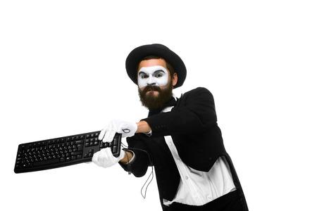 mimo: Mime enojado como un hombre de negocios est� destruyendo un teclado. aislado en fondo blanco Foto de archivo