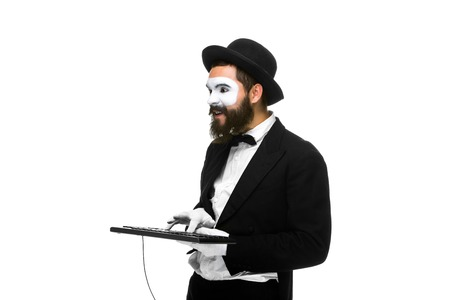 mime as a businessman holding a keyboard, isolated on white background.  concept of confident user
