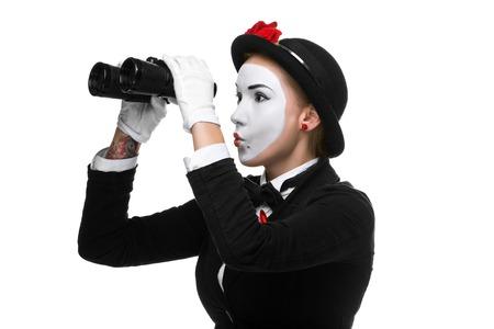 mimo: Retrato de la mujer que busca como mimo con binoculares aisladas sobre fondo blanco. Concepto intensa b�squeda