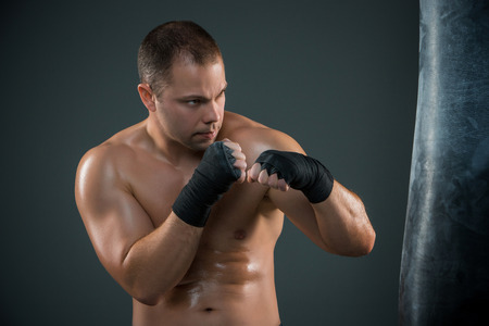 beat the competition: Young boxer boxing over black background