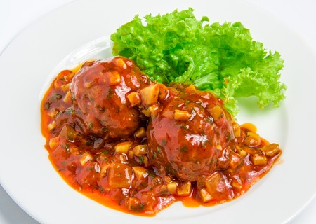 Veal meatballs with bacon in a tomato sauce with mushrooms on white plate photo