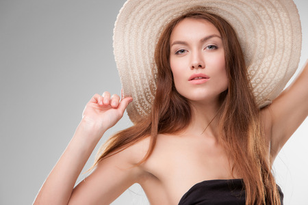 Close-up portrait of beautiful girl with hat posing in studio on gray background photo