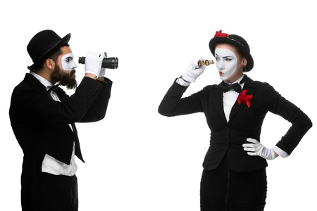 Two memes as business people looking at each other through binoculars isolated on white background. concept of suspicion and mistrust photo