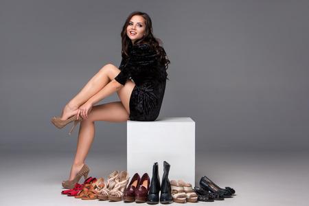 tienda de zapatos: foto de sentarse muchacha atractiva joven probándose zapatos de tacón alto sobre un fondo gris