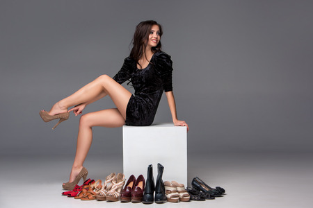 high heeled: picture of sitting young attractive girl trying on high heeled shoes on a gray background