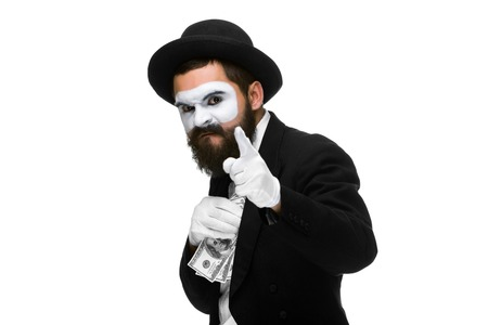 venal: mime as a businessman in a  suit putting money in his pocket. isolated on a white background. concept  love of money and  greed