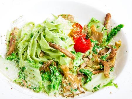 queso rayado: pastas verde con carne, queso rallado, tomates, repollo y salsa en un plato blanco