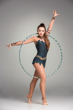 slim girl: teenager doing gymnastics exercises with colorful hoop on a gray background