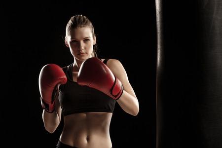 krásná žena s červenými rukavicemi boxu je na černém pozadí Reklamní fotografie