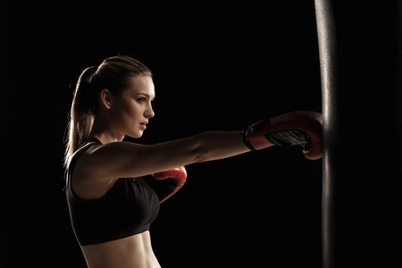 young female: beautiful woman with the red gloves is boxing on black background